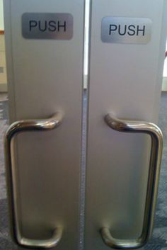 """doors with handles and signs above the handles reading """"push"""""""